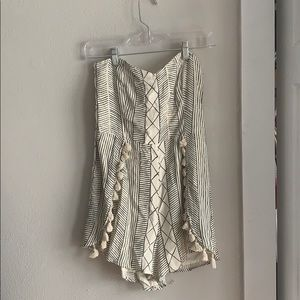 Patterned strapless romper with tassels.